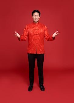 Joyeux nouvel an chinois. bel homme asiatique avec le geste de la main ouverte d'introduire isolé sur fond rouge.