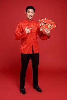 Joyeux nouvel an chinois. homme asiatique tenant angpao ou cadeau monétaire de paquet rouge sur rouge. le texte signifie beaucoup de chance.