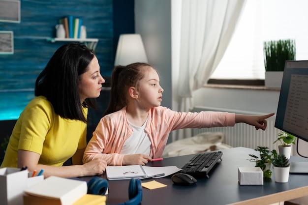 Joyeux parent assis à côté de sa fille faisant ses devoirs scolaires ensemble