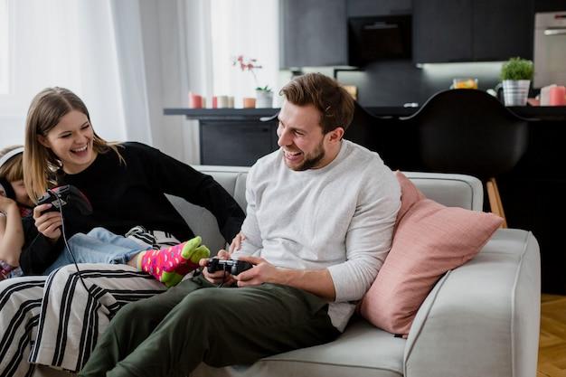 Joyeux parents jouant à des jeux vidéo près de la fille