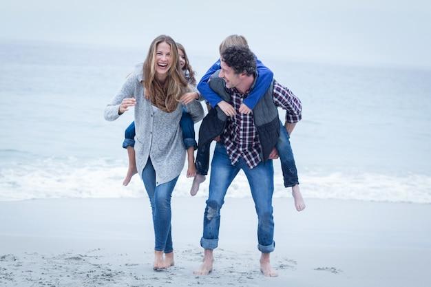 Joyeux parents portant des enfants sur le dos au bord de la mer