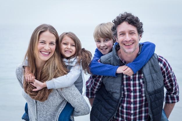 Joyeux parents portant des enfants à la plage
