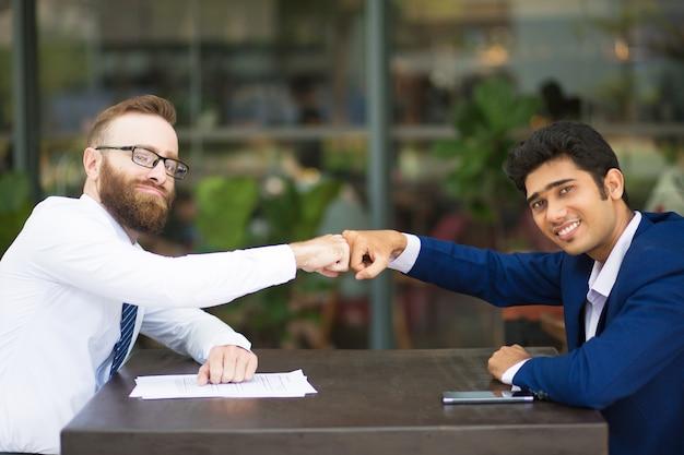 Joyeux partenaires d'affaires faisant poing bosse