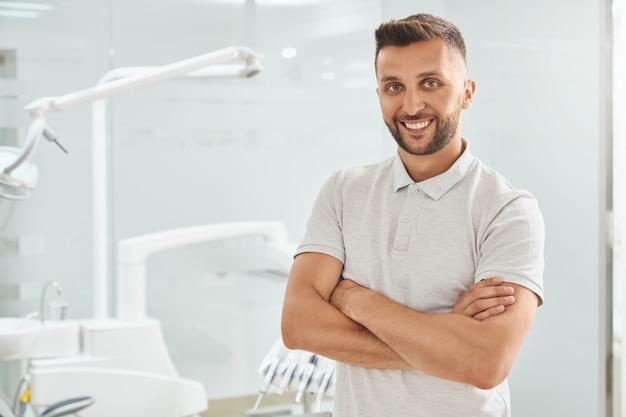 Joyeux patient debout avec ams plié en clinique dentaire