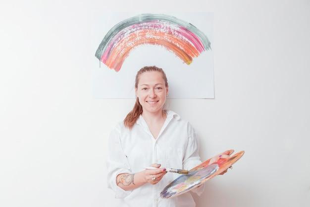 Joyeux peintre avec palette et pinceau en studio
