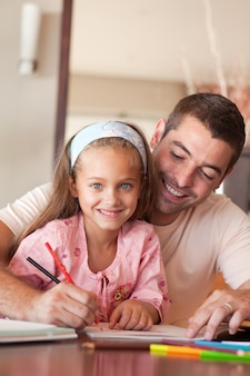 Joyeux père aidant sa fille à faire ses devoirs