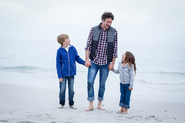 Joyeux père avec des enfants au bord de la mer