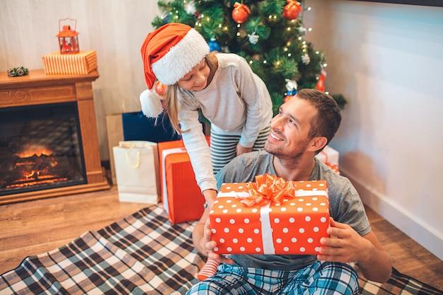 Joyeux père et fille se regardent et sourient.