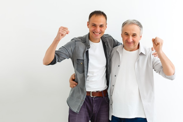 Joyeux père et fils étreignant et posant ensemble isolés sur mur blanc