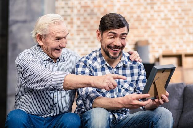 Joyeux père et fils regardant un cadre photo et souriant