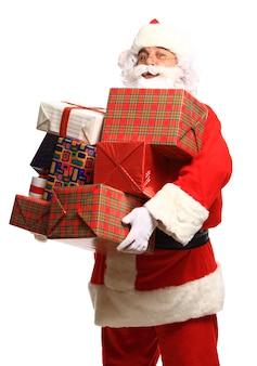 Joyeux père noël avec des cadeaux de noël regardant la caméra