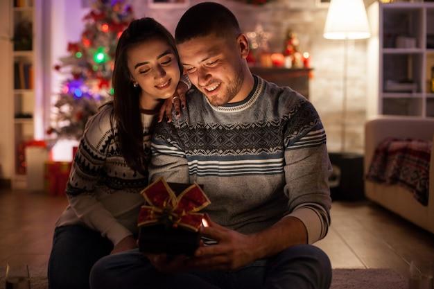 Joyeux petit ami ouvrant la boîte-cadeau magique de sa petite amie à noël.