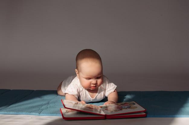 Joyeux petit bébé se trouve sur un lit et ressemble à un album photo