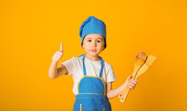 Joyeux petit chef dans un chapeau et un tablier tient une spatule en bois et une cuillère sur une surface jaune avec un espace pour le texte