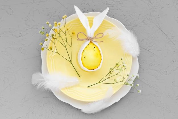 Joyeux petit-déjeuner ou branche de pâques. sur plaque jaune œuf coloré avec oreilles de lapin et décorations sur surface grise ultime.
