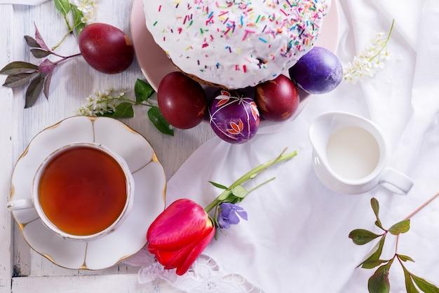 Joyeux petit-déjeuner de pâques avec une tasse de thé en porcelaine blanche, des œufs colorés et un gâteau de pâques fraîchement sorti du four.