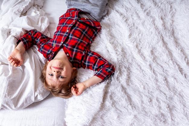 Joyeux petit enfant bouclé avec visage souriant allongé sur le lit