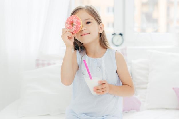 Joyeux petit enfant de sexe féminin pose dans la chambre à coucher avec délicieux beignet et lait frappé