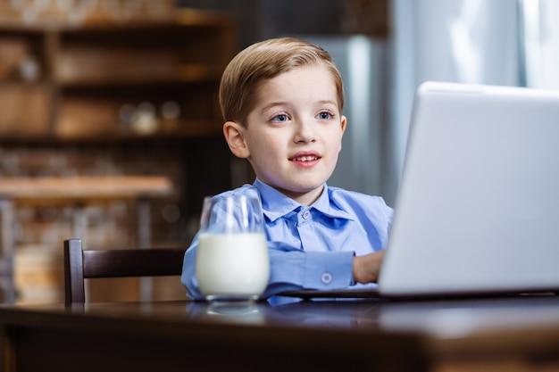Joyeux petit garçon à l'aide de son ordinateur portable tout en se reposant dans la cuisine