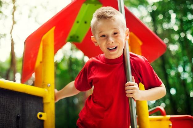 Joyeux petit garçon sur l'aire de jeux