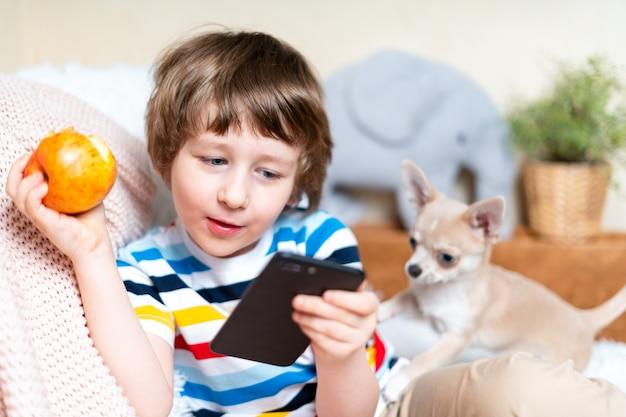 Joyeux petit garçon jouant à un jeu en ligne en regardant une vidéo sur un téléphone portable et en mangeant une pomme en souriant