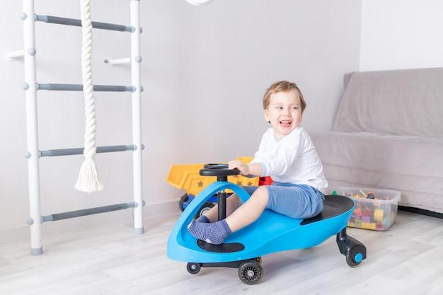 Joyeux petit garçon jouant à la maison, chevauchant une machine à écrire, le concept d'un jeu d'enfant
