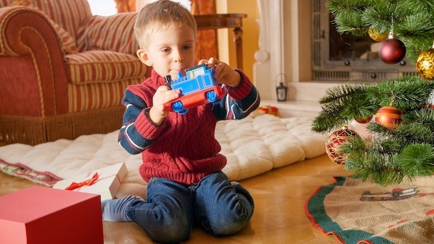 Joyeux petit garçon regardant et souriant au train jouet qu'il a eu à noël. enfant recevant des cadeaux le nouvel an
