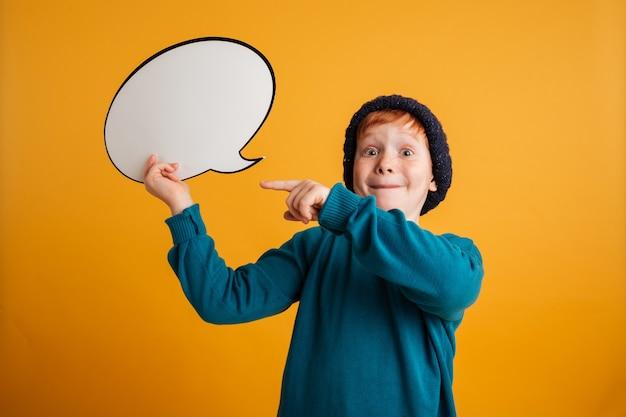 Joyeux petit garçon rousse tenant une bulle de dialogue.