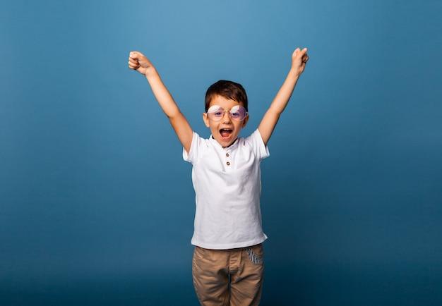 Joyeux petit garçon triomphant avec les mains levées sur fond bleu.
