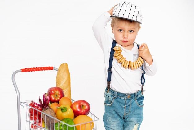 Joyeux petit garçon en vêtements décontractés debout en studio avec panier de nourriture saine. shopping, discount, concept de vente