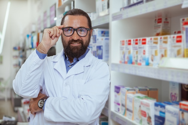 Joyeux pharmacien vendant des médicaments dans sa pharmacie