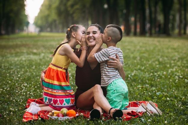 Joyeux pique-nique en famille. mère et deux enfants dans le parc naturel