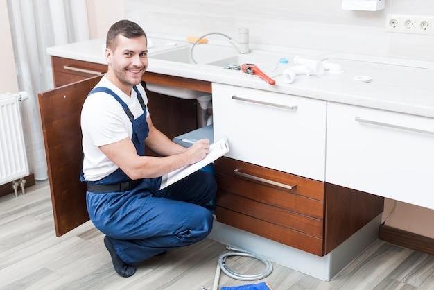 Joyeux plombier écrivant en papier sur la cuisine