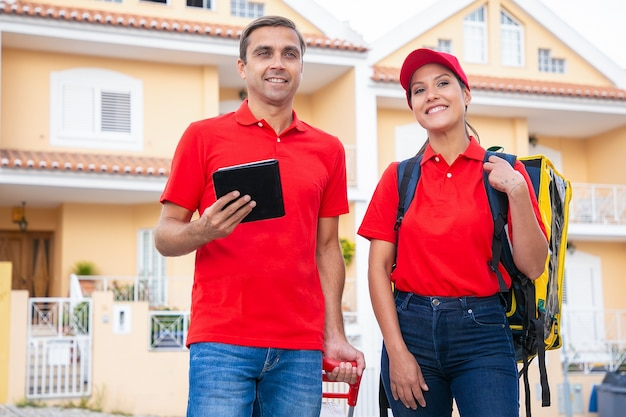 Joyeux postiers debout, souriant et travaillant ensemble. heureux courriers livrant la commande dans un sac thermique et portant des chemises rouges. homme tenant la tablette. service de livraison et concept d'achat en ligne