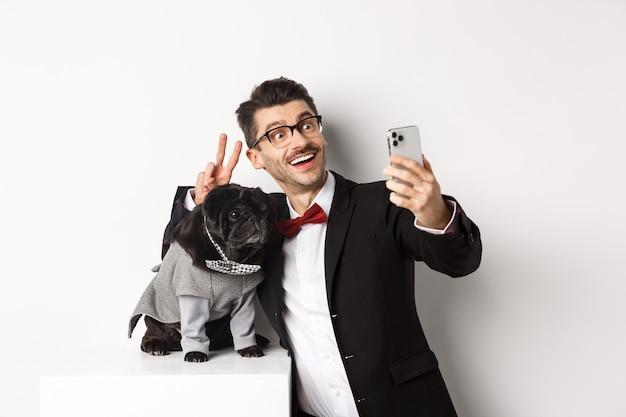 Joyeux propriétaire de chien en costume célébrant noël avec un chien, prenant un selfie sur un smartphone près d'un mignon carlin noir en costume, fond blanc.