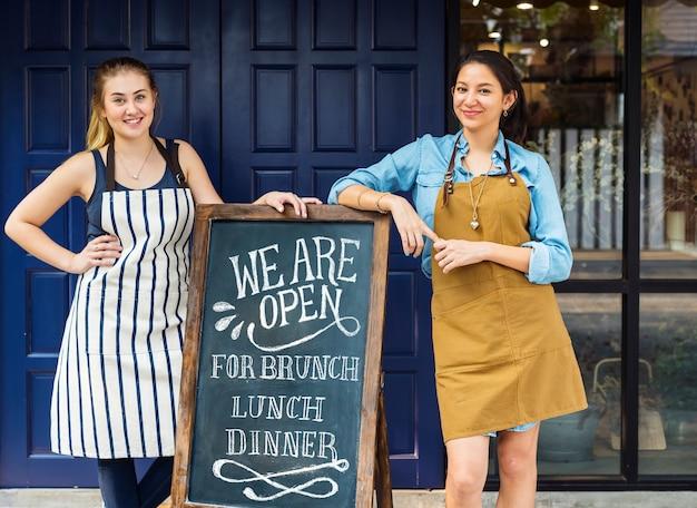 Joyeux propriétaires d'entreprises debout avec tableau noir ouvert