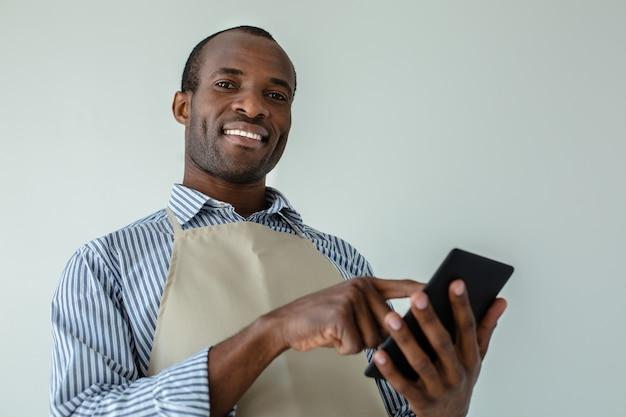 Joyeux serveur recevant la commande tout en tenant une tablette