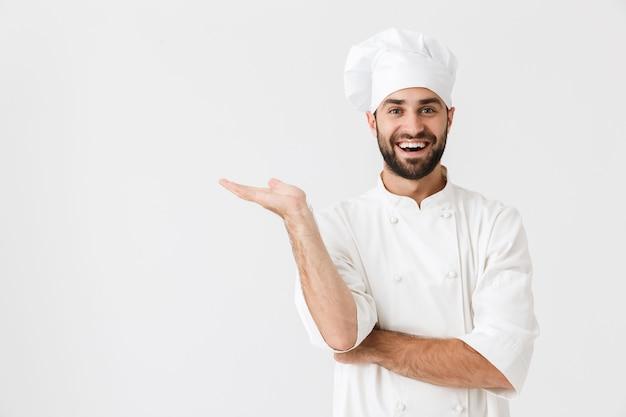 Joyeux sourire heureux jeune chef posant en uniforme montrant le fond.