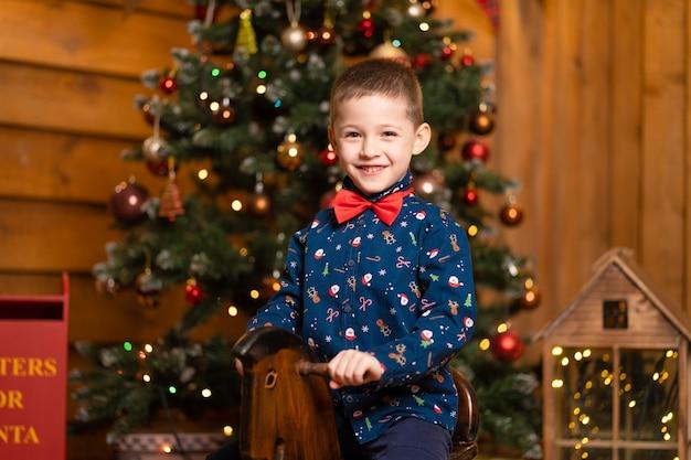 Joyeux souvenirs des vacances de noël pour les enfants. le père noël a donné un cheval de balançoire à un petit garçon