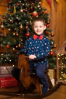 Joyeux souvenirs des vacances de noël pour les enfants. le père noël a donné un cheval de balançoire à un petit garçon.