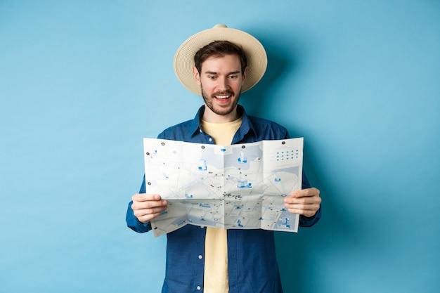 Joyeux touriste en chapeau d'été planification itinéraire de voyage en vacances, regardant la carte touristique et souriant excité, debout sur fond bleu.