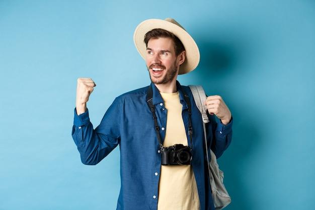 Joyeux touriste se réjouissant en vacances, célébrant les vacances d'été, montrant le geste de la pompe de poing et disant oui avec un visage satisfait, regardant de côté, fond bleu.