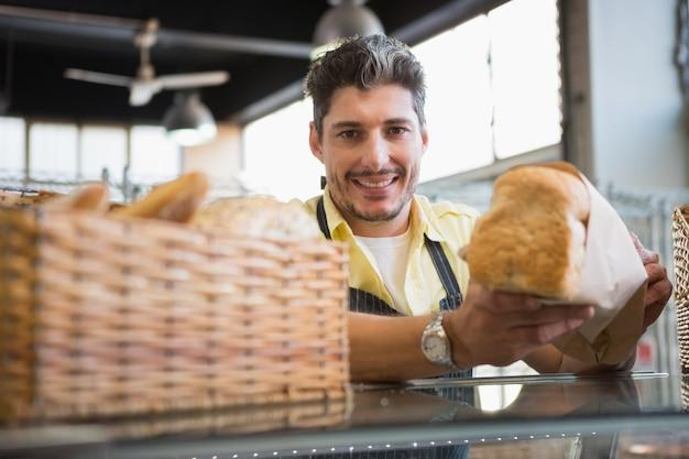Joyeux travailleur debout et présentant un pain
