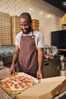 Joyeux travailleur masculin en tablier regardant une pizza au pepperoni dans une boîte en carton et souriant