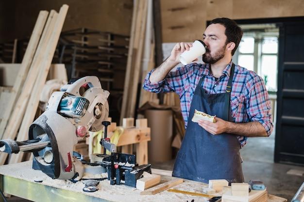 Joyeux travailleur de menuiserie en train de déjeuner manger un sandwich dans un atelier