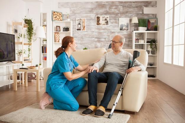 Joyeux vieil homme dans une maison de soins infirmiers ayant une conversation avec une femme médecin.