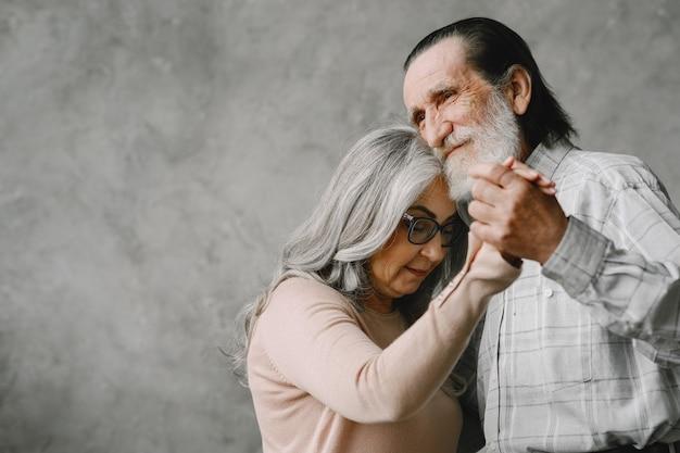 Joyeux vieux couple romantique à la retraite dansant dans le salon.