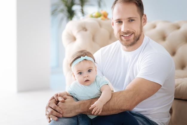 Joyeux week-end en famille. jeune père souriant positif assis à la maison et étreignant sa fille tout en exprimant sa positivité