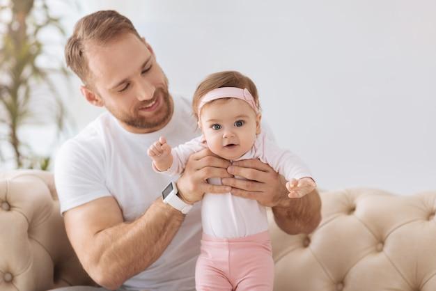 Joyeux week-end de père. heureux homme impliqué athlétique assis sur le canapé à la maison et étreignant son enfant tout en exprimant des émotions tendres et en s'amusant