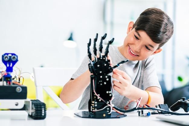 Joyeux whizzkid intelligent expérimentant la main robotique humanoïde tout en développant ses compétences
